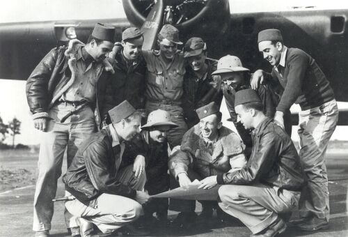 black and white photo of young men in front of a bomber looking at a map