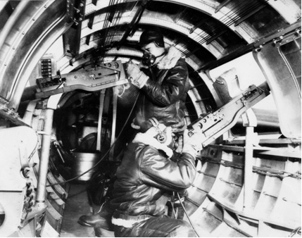 Waist gunners in position inside aircraft