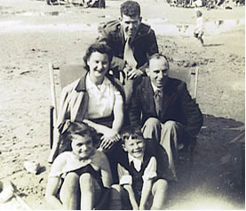 O'Neil poses on the sandy beach with a British family of four, seated
