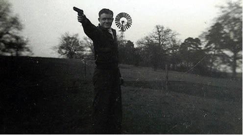 Staff Sgt Nealms stands on a beautiful hillside pointing his pistol. A windmill can be seen at the top of the hill.